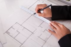 Close-up of female architect drawing blueprint Royalty Free Stock Photos