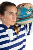 Close up of female athlete holding rugby ball while looking away Royalty Free Stock Photo