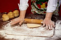 Close up of female baker hands kneading dough and making bread with a rolling pin Royalty Free Stock Photos
