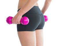 Close up of female bottom while training with pink dumbbells. On white background Stock Images
