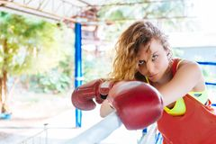 Female boxer inside thai boxing ring. angree emotions. Close up of a female boxer inside a boxing ring. Woman boxer at a boxing studio Royalty Free Stock Image