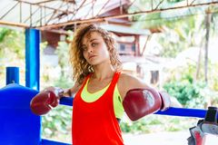 Female boxer inside thai boxing ring. angree emotions. Close up of a female boxer inside a boxing ring. Woman boxer at a boxing studio Stock Images