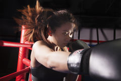 Close up of female boxer throwing a punch, hair in motion Royalty Free Stock Images