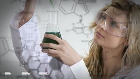 Scientist working on chemicals. Close up of a female Caucasian scientist mixing chemicals in a flask. The clip has digital effects of chemical equations in the stock video