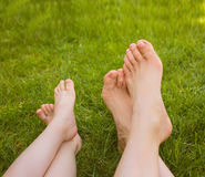 Close up female and child legs lying on the grass. Royalty Free Stock Photos
