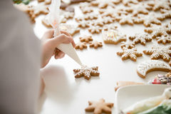 Close up of female confectioner hands icing gingerbread stars. Close up of female confectioner hands decorating gingerbread stars with icing sugar using selfmade Royalty Free Stock Photos