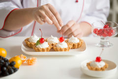 Close up of female confectioner hands topping custard tarts Royalty Free Stock Images