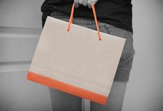 Close-up of female customer holding paper shopping bag. Consumer behavior concept stock photo