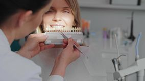 Dentist choosing color teeth from palette. Close up of female dentist choosing color teeth from palette stock footage
