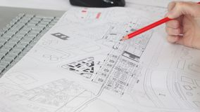Close up of female design engineer sits at the desk in her office, blueprints laying