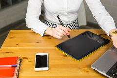 Close-up of Female designer in office working with digital graphic tablet and laptop. Photography retoucher sitting at Royalty Free Stock Photos