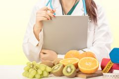 Close up of a Female Dietician With Fresh Vegetables and fruits. On a green background royalty free stock photos
