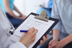Close Up of a female doctor filling  out application form while talking to patient. Medicine and health care concept.  Royalty Free Stock Images