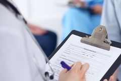 Close Up of a female doctor filling  out application form while talking to patient. Medicine and health care concept.  Stock Image