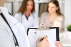 Close-up of a female doctor while filling up medical prescription Royalty Free Stock Photography