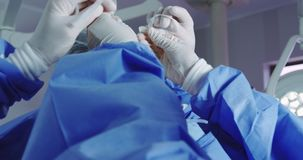 Close-up of female doctor helping male doctor to wear surgical mask in operation theater stock video