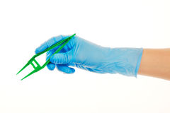 Close up of female doctor's hand in blue sterilized surgical glove with green plastic forceps against white Royalty Free Stock Photo