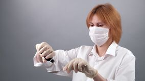Close-up of female doctor`s hands dripping drugs from a bottle to spoon. Woman doctor in medical mask in soft focus