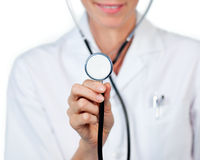 Close-up of a female doctor showing a stethoscope. Against a white background Royalty Free Stock Photography