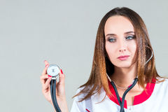 Close-up Female doctor standing in a robe and listens with a ste. Female doctor standing in a robe and listens with a stethoscope, isolated on a light background Stock Image