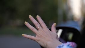 Close-up. A female driver during a trip stuck her hand out and makes waves through the air. 4K Slow Mo stock footage