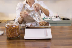 Close-up of a female employee measuring spice on weight scale in store Stock Image