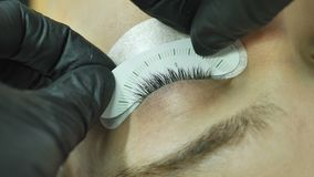 Close-up female eye with substrate on the eyelid of a beauty salon master applies a stencil measuring the size of