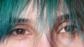 Close-up of female eyes. Green hair in front of eyes.  stock video