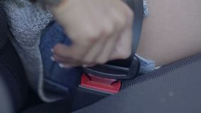Close up of female fastening safety belt in car stock video footage