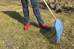 Close-up of female feet in blue jeans and red rubber boots with rakes, garden work. Close - up of female feet in blue jeans and red rubber boots with rakes Royalty Free Stock Image