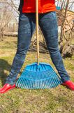 Close-up of female feet in blue jeans and red rubber boots with rakes, garden work. Close - up of female feet in blue jeans and red rubber boots with rakes Royalty Free Stock Photo
