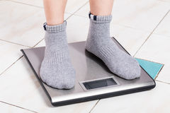 Close up female feet on digital weighting scale. Royalty Free Stock Image