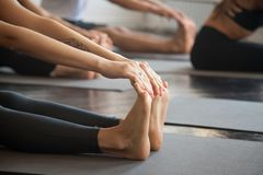 Close up of female feet, paschimottanasana pose. Close up of female feet, group of young sporty people practicing yoga lesson with instructor, sitting in Stock Images