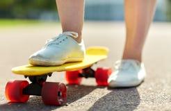Close up of female feet riding short skateboard Royalty Free Stock Photo