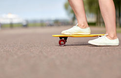 Close up of female feet riding short skateboard Stock Image