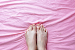 Close Up of Female Feet and Slim Legs on the Pink Bed, Feet in the Bedroom Background at Home Royalty Free Stock Photos