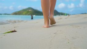 Close up female feet walking barefoot on sea shore at sunset. Slow Motion. Close up female feet walking barefoot on sea shore at sunset stock video