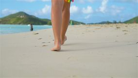 Close up female feet walking barefoot on the beach. Slow Motion. Close up female feet walking barefoot on sea shore at sunset. Slow Motion stock video footage
