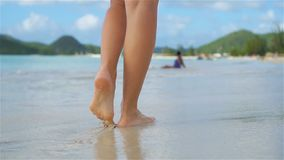 Close up female feet walking barefoot on the beach. Slow Motion. Close up female feet walking barefoot on sea shore at sunset. Slow Motion stock footage