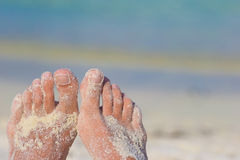 Close up of female feet on white sandy beach Royalty Free Stock Photography
