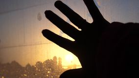 Close up of female hand touches wet window in a car against sunset background. Close up of female finger wiping wet window against sunset background stock video
