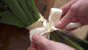 Close-up of female fingers tied in bow ribbon on bouquet stock video