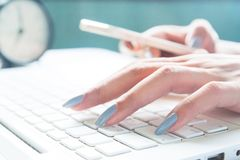 Close up of female fingers using laptop and mobile device, Working woman and Online shopping Royalty Free Stock Photos