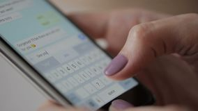 Close-up of female fingers write message on smartphone to a friend. Woman is typing text on touch screen in a popular instant messenger with emoticons stock footage