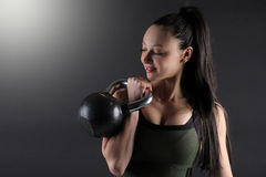 Close up of a female fitness model holding a kettlebell in the rack position. Image of a fit beautiful woman holding a kettlebell weight on a dark background Stock Photos