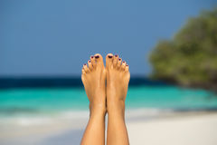 Close-up of female foot in the blue water on the tropical beach. Royalty Free Stock Photos