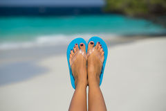 Close-up of female foot in the blue water on the tropical beach. Stock Photography
