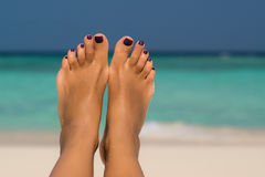 Close-up of female foot in the blue water on the tropical beach. Royalty Free Stock Photo