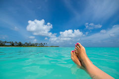 Close-up of female foot in the blue water on the tropical beach. Stock Photos