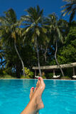 Close-up of female foot in the blue water on the tropical pool. Stock Photo